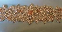 Rose gold beads with rhinestone sash.